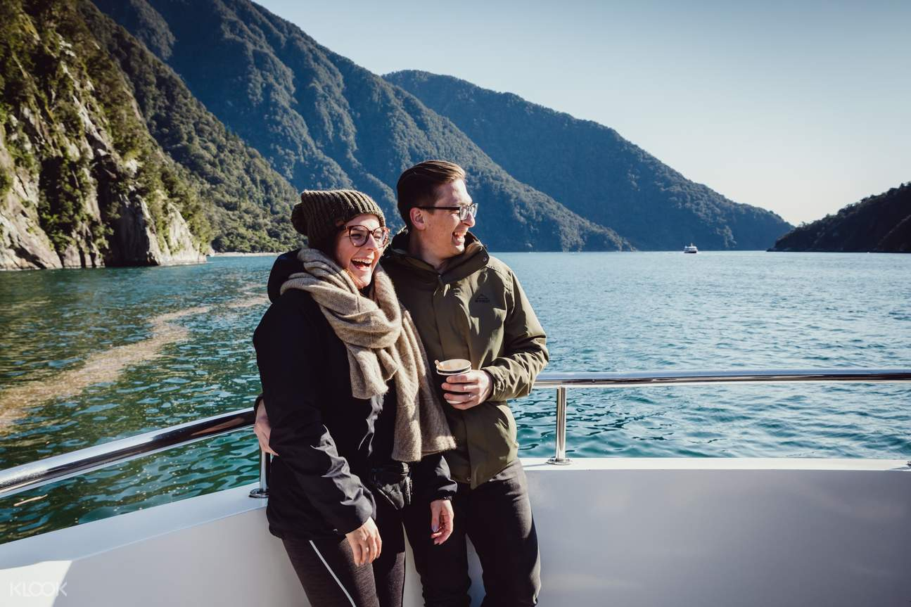 a couple having their picture taken while riding a boat along the Milford Sound